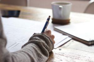człowiek piszący przy biurku