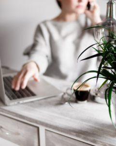 kobieta pisząca na klawiaturze, odbierająca telefon