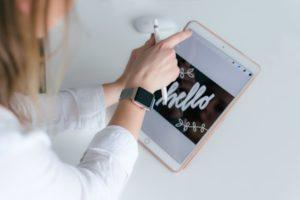 tablet, napis hello, dłoń